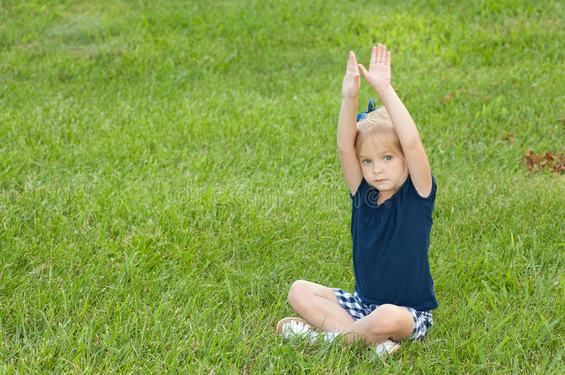One girl sitting in grass stock photo
