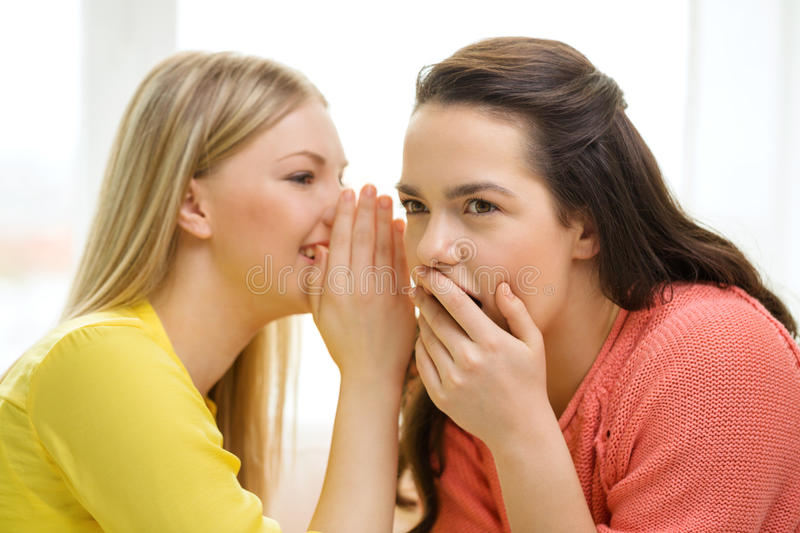 One girl telling another secret stock image