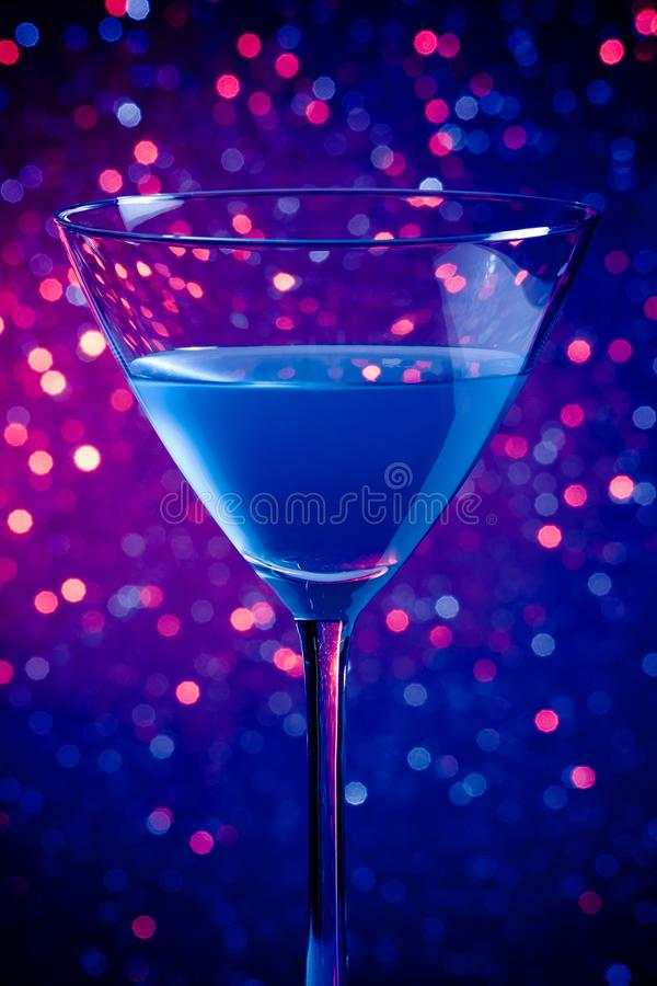 One glass blue cocktail on blue and violet tint light background. One glass blue cocktail on blue and violet tint light bokeh background royalty free stock photos
