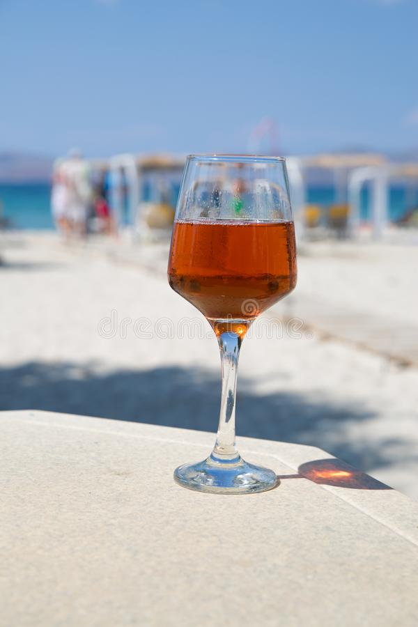 One glass of cold rose wine served on the beach. royalty free stock photo