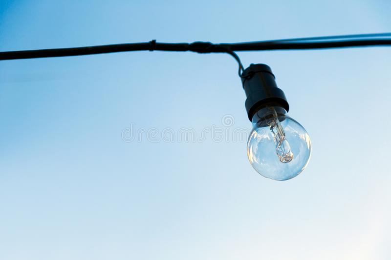 Glass light bulb off, hanging on a cable in exterior. stock images
