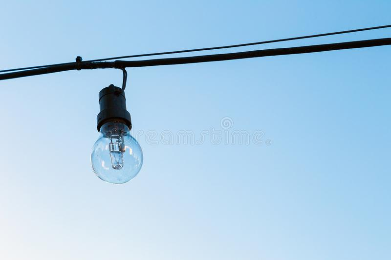 Glass light bulb off, hanging on a cable in exterior. One glass light bulb off, hanging on a cable in exterior. The blue sky at background royalty free stock photos