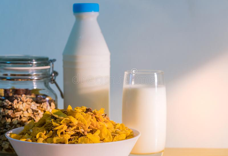 One glass of milk and milk bottle with blank label put on wood table near bowl of cereal with spoon. Calcium food breakfast. For children before go to school in stock photo