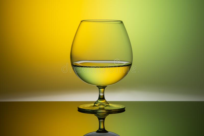 One glass glass of water on a multicolored background. One glass glass of water on multicolored background royalty free stock photos