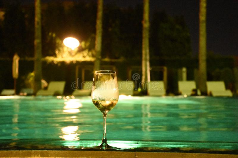 One glass of wine at swim pool at night, have noise technique and defocus royalty free stock images