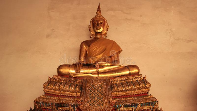 One Golden Buddhas Statue On Gilded Stucco Bench. Religion. Golden Buddhas Image symbol and traditional of Buddhism in Bangkok Thailand royalty free stock photography