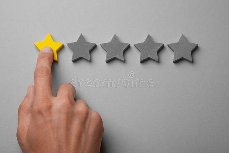 One golden yellow stars out of five. Man points finger at the star, puts rating. Recalls stock image