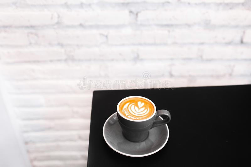 One gray cup of fresh cappuccino on black table. Background of white textured brick wall, loft style interior. Black and white minimalist style. Empty place stock image