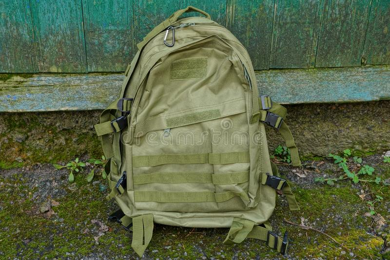 Green army backpack stands on the ground near the wall in the street. One green army backpack stands on the ground near the wall in the street royalty free stock photography