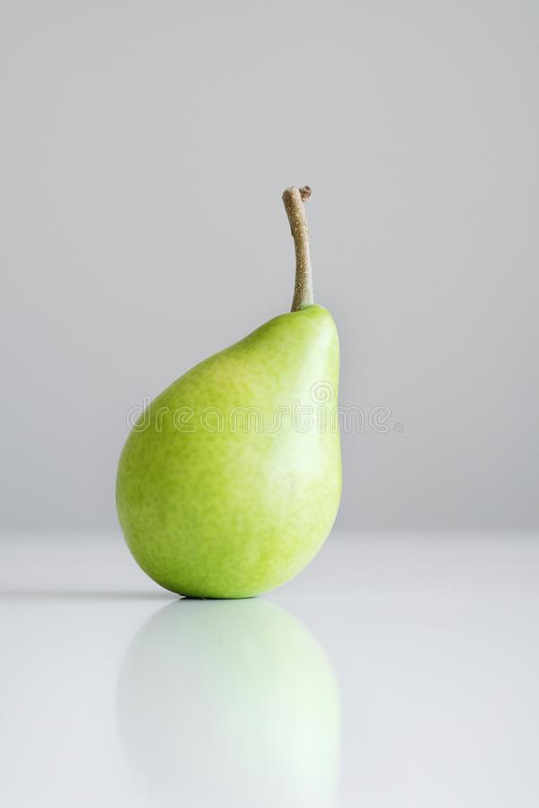 One green yellow pear with a twig stands on a white table, a reflection, a bright light, minimalism and free space for stock images
