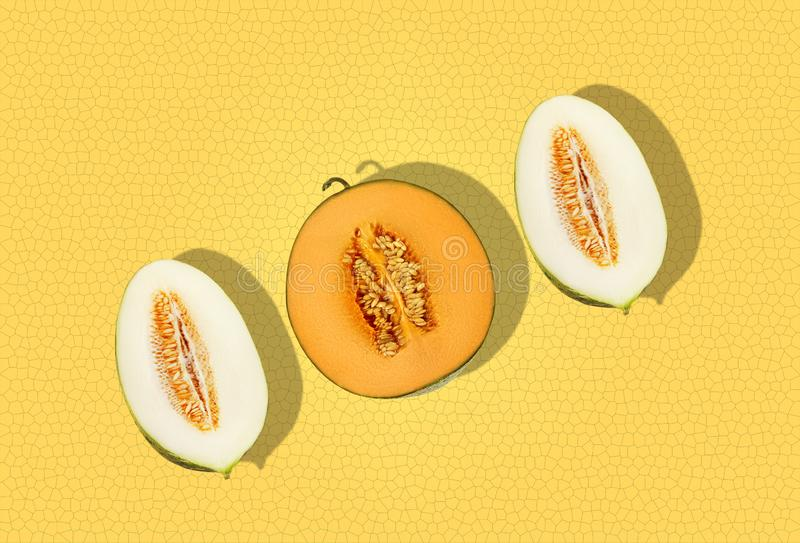 One half of cantaloupe melon and two halves of tendral one in cross-section, on yellow background, copy space for text royalty free stock photo