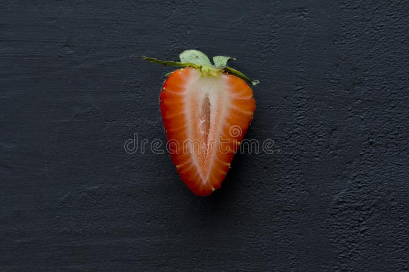 One half of strawberry, cut red beautiful strawberry close-up, on a black dark concrete background. Macro shooting. Fruit erotica. Flat Lay, Top View, Copy royalty free stock photography