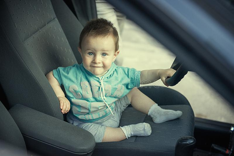 One and a half year old child sits behind the wheel of a car royalty free stock photos