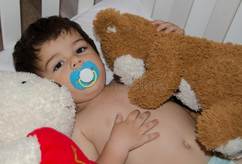 One and half years old baby boy in the cot hugging his teddy bear stock images