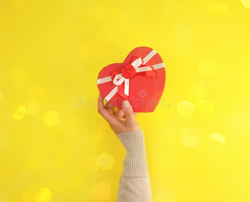 one hand hold a paper closed red box in the shape of a heart royalty free stock images