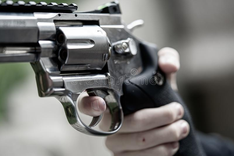 One hand is large silver heavy revolver and aims into the air royalty free stock images