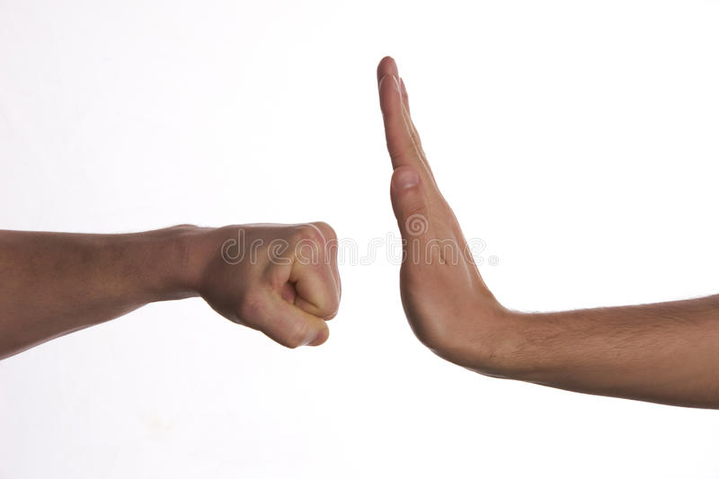 One hand preventing punch attack of another hand royalty free stock image