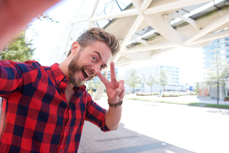 One handsome smiling man taking fun selfie. And making peace hand sign royalty free stock photo