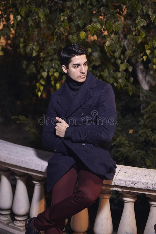 One handsome young man, 20-29 years old, posing, autumn clothes, looking sideways sitting on street marble fence. night time, dark royalty free stock photos