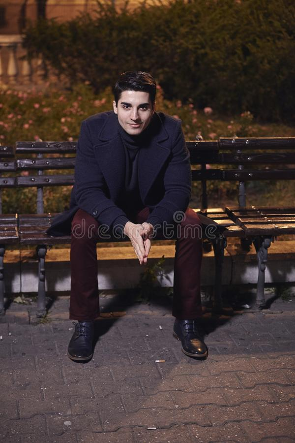 One handsome young man, 20-29 years old, posing, autumn clothes, sitting bench on city square. night time, dark royalty free stock image
