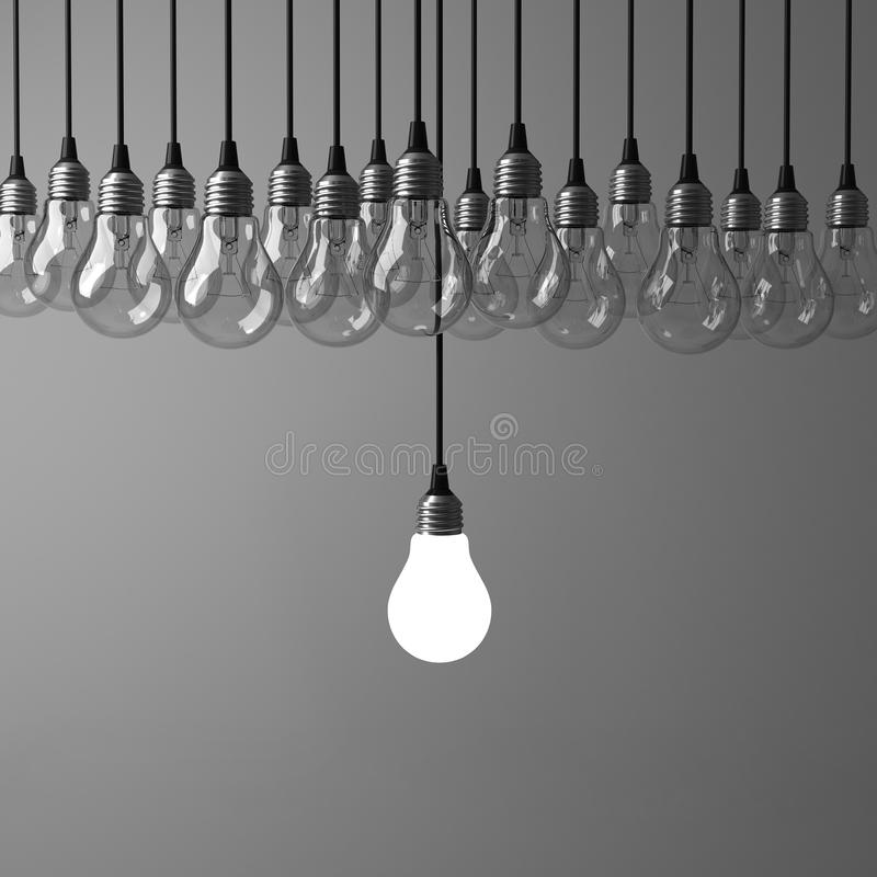 One hanging light bulb glowing different and standing out from unlit incandescent bulbs on dark grey background stock photography