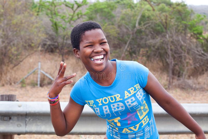 One happy african beautiful young girl in blue t-shirt smiling with white teeth and chewing gum outdoors close up stock photography