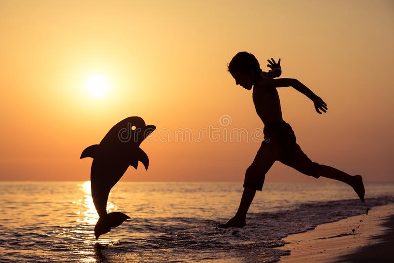 One happy little boy playing on the beach at the sunset time. stock images