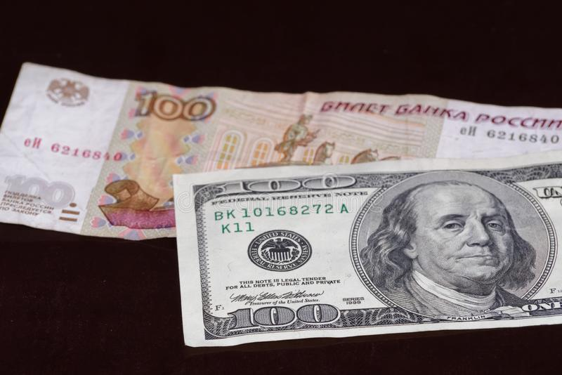 One hundred american dollars banknote above russian one hundred rubles stock photography