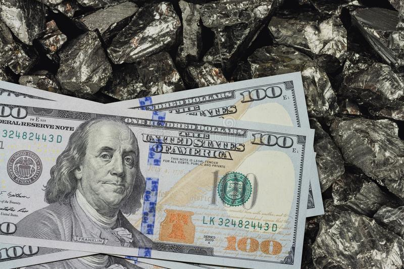 One hundred dollar banknotes on coal mine close up. Mining industry concept with dollars and coal stock image