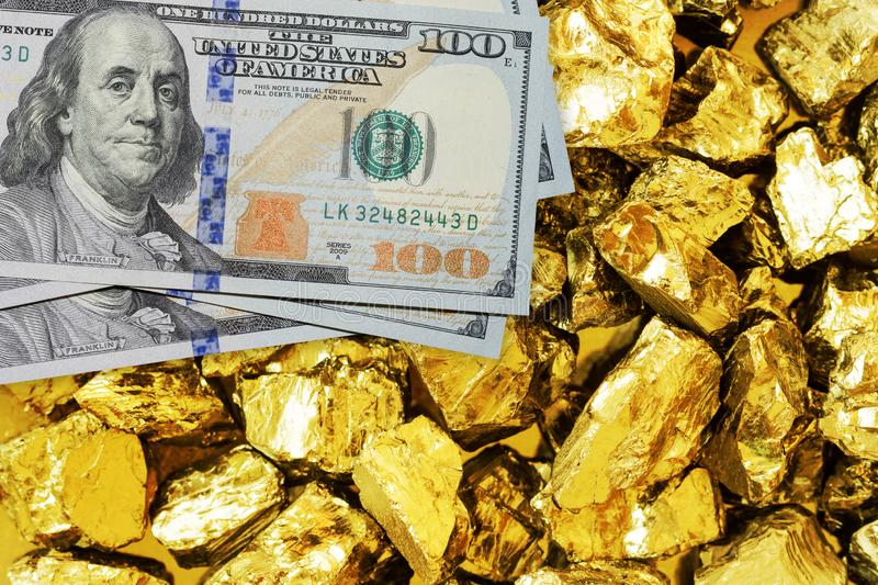 One hundred dollar banknotes on gold mine close up. Mining industry concept with dollars and gold stock image