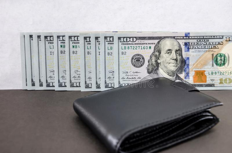 One hundred dollar bills folded in a row and a black wallet royalty free stock photos