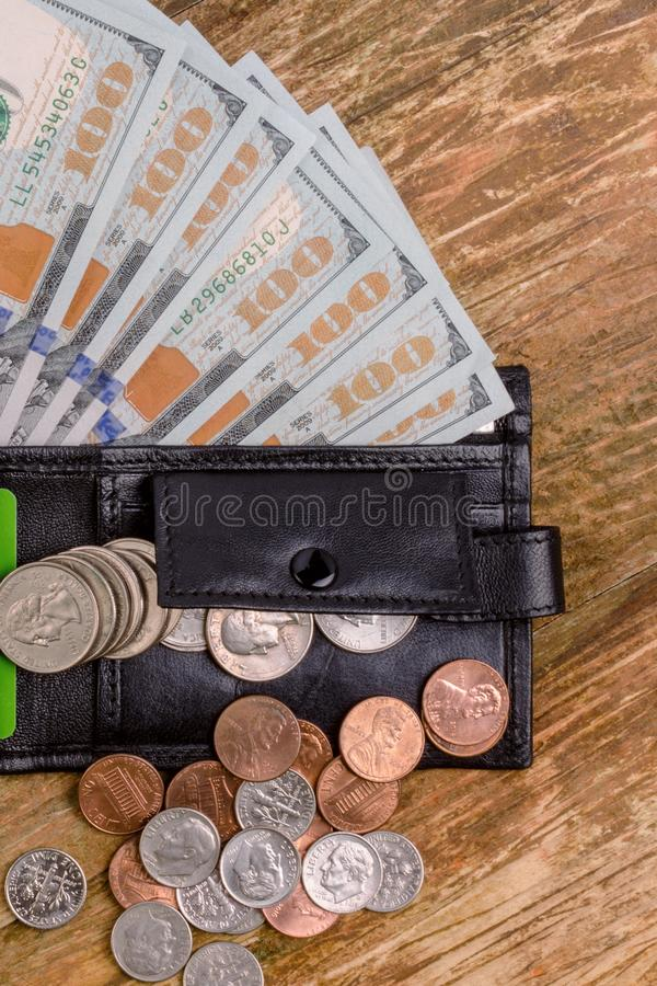 One hundred dollars banknote reach out out of a black old purse. stock image