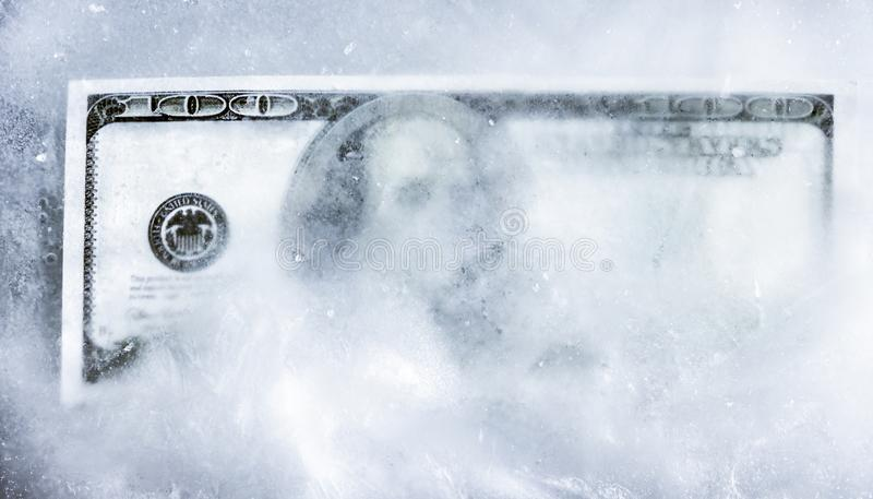 One hundred dollars frozen in ice. account freezing. stock photography
