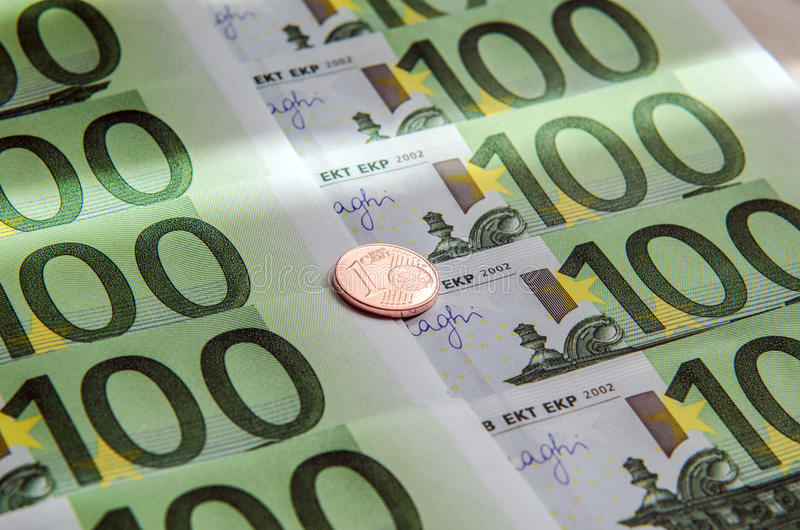 One hundred Euro banknotes and coin of one cent. stock image