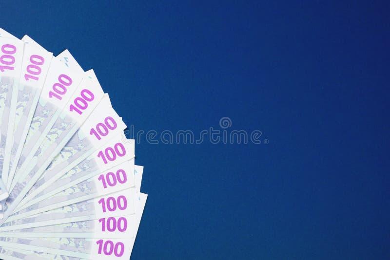One hundred euro notes on blue background stock image