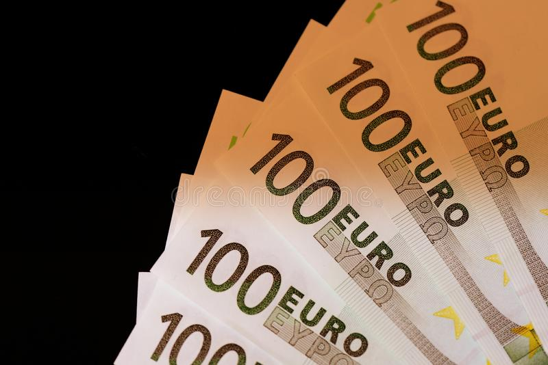 One hundred euro notes on a dark background. Brown color toned royalty free stock image