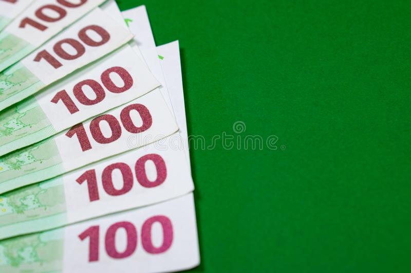 One hundred euro notes on green background stock photo