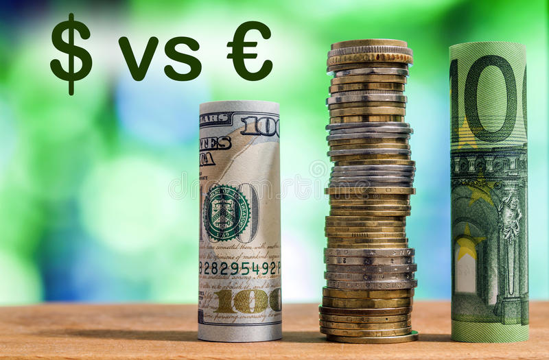 One hundred euro and one hundred US dollar rolled bills banknote. S, with euro coins and american cents on green blurred bokeh background. Dollar vs Euro concept royalty free stock photos