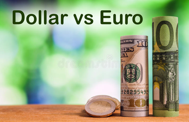 One hundred euro and one hundred US dollar rolled bills banknote. S, with euro coins and american cents on green blurred bokeh background. Dollar vs Euro concept royalty free stock images