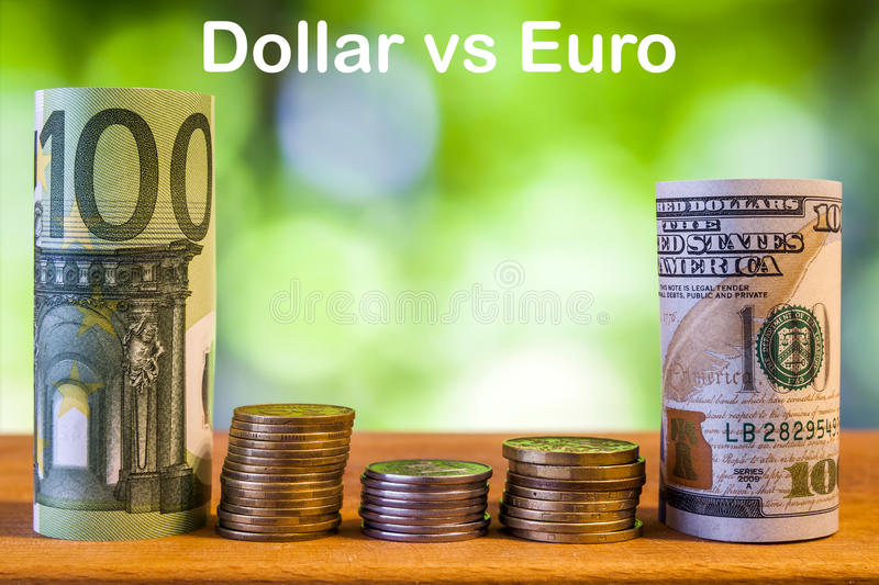 One hundred euro and one hundred US dollar rolled bills banknote. S, with euro coins and american cents on green blurred bokeh background. Dollar vs Euro concept royalty free stock photo