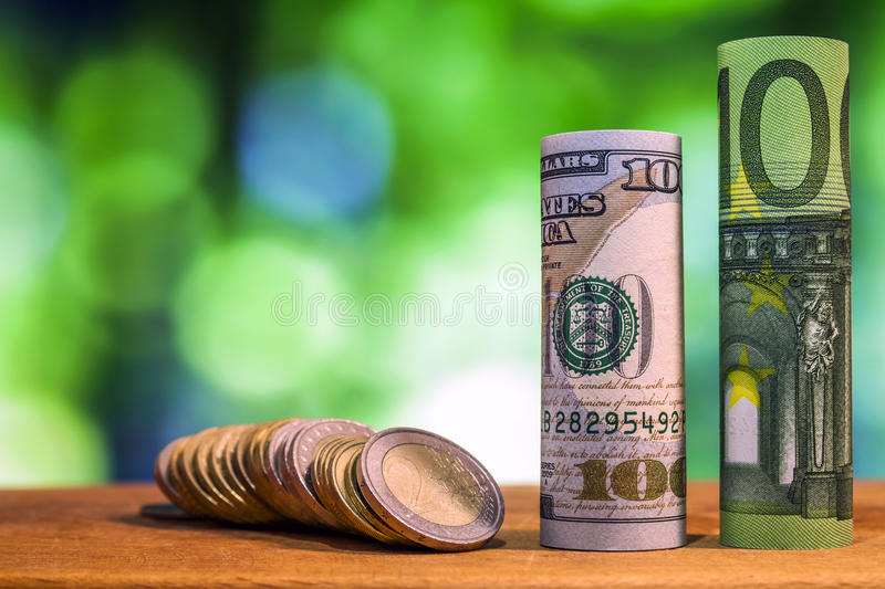 One hundred euro and one hundred US dollar rolled bills banknote. S, with euro coins and american cents on green blurred bokeh background stock images