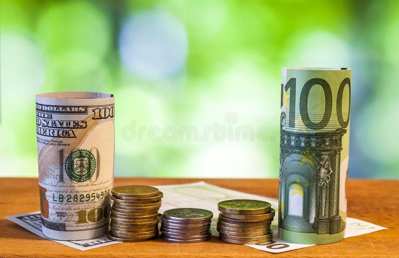 One hundred euro and one hundred US dollar rolled bills banknote stock photos