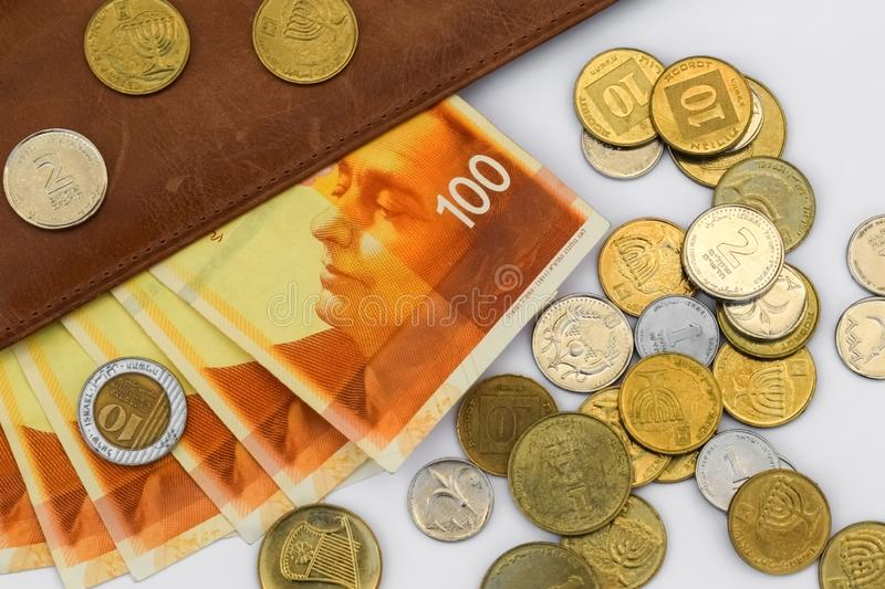 One hundred shekels bills surrounded by many coins on a white background stock photos