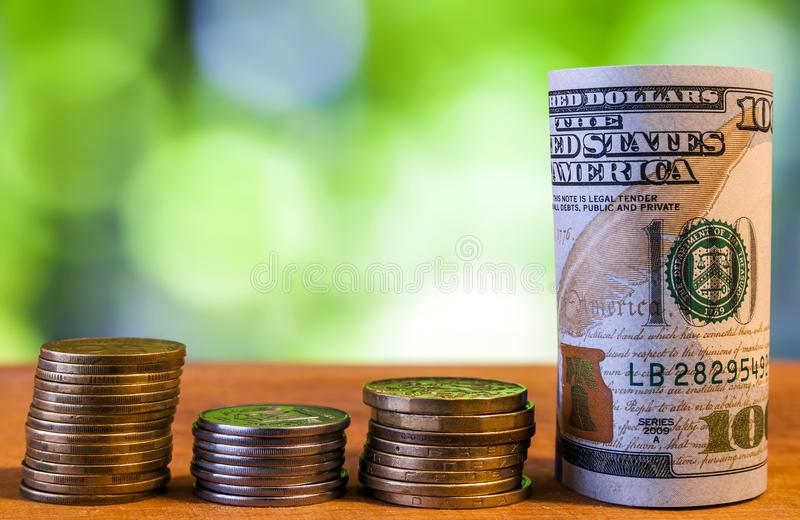 One hundred US dollar bills banknotes, with american cents coins. On green blurred bokeh background stock photos