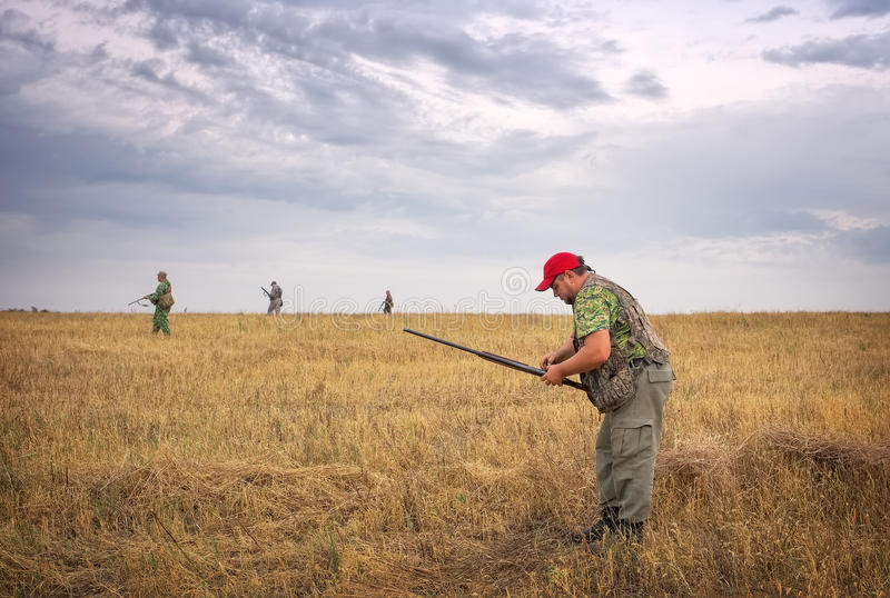 One hunter charges ammo and other hunters moving. Through the field stock images