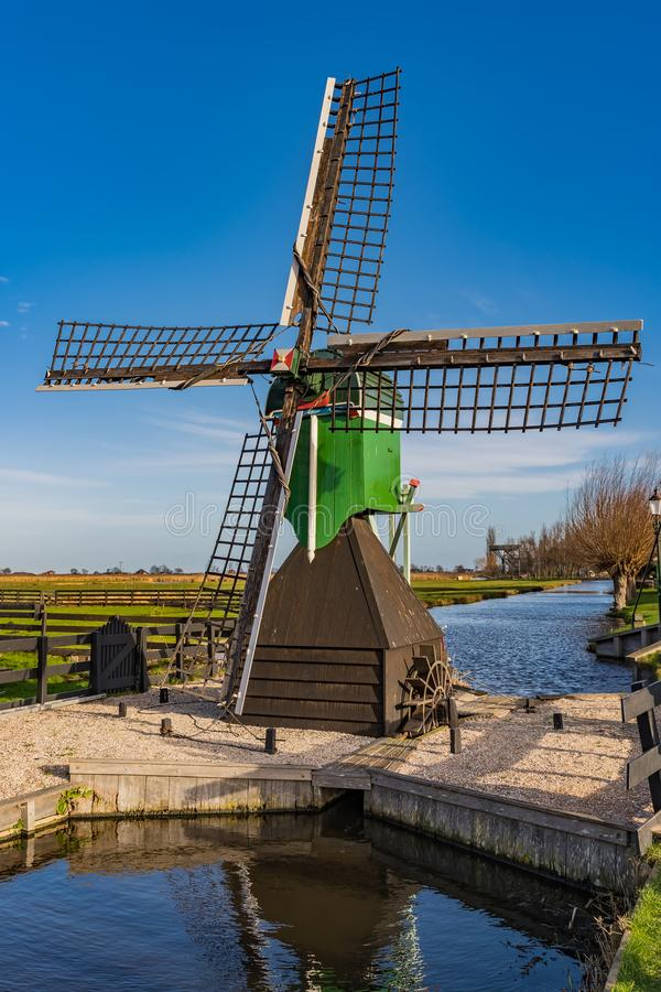 Windmill isolated on the water. One isolated windmill on the water with blue sky stock photos