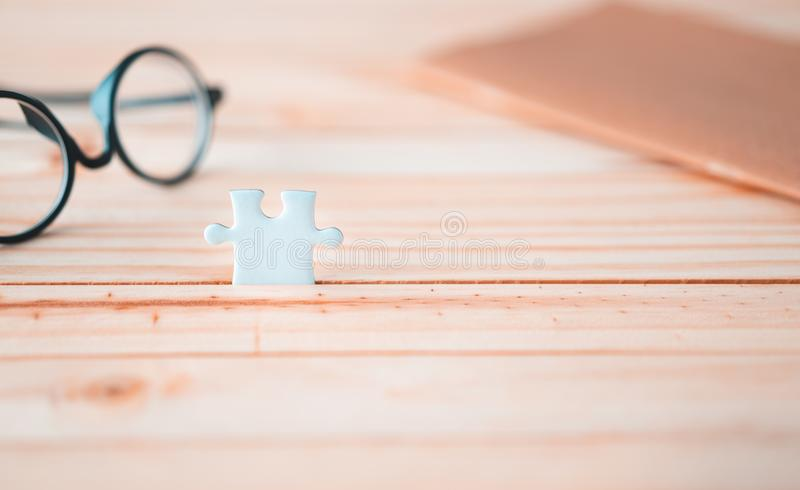One jigsaw puzzle on wooden table with blurred glasses stock photography