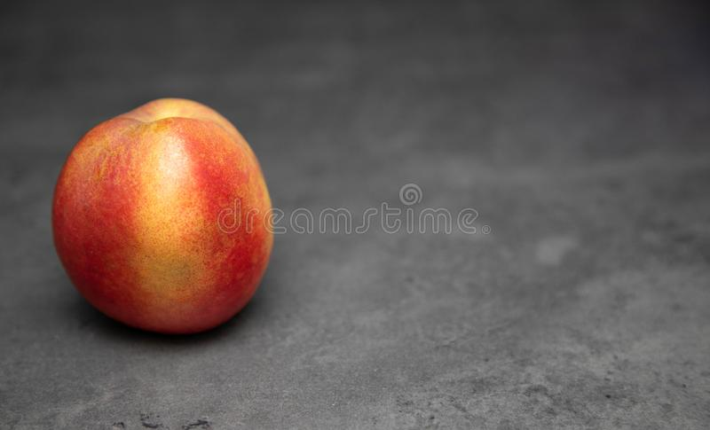 One juicy, ripe, nectarine on a gray background. Nectarine on the table. Place for text royalty free stock photo
