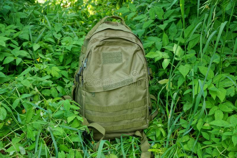 One large backpack stands in the green grass with leaves and vegetation royalty free stock image