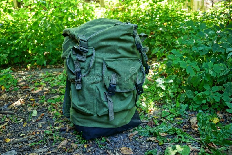One large full backpack stands on the ground and in the green grass stock images